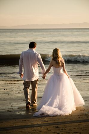 Young couple wearing white getting married on a sunny day with a beach setting.