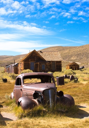 jalopy: 1937 Chevy without wheels abandoned in the desert with house as a background.