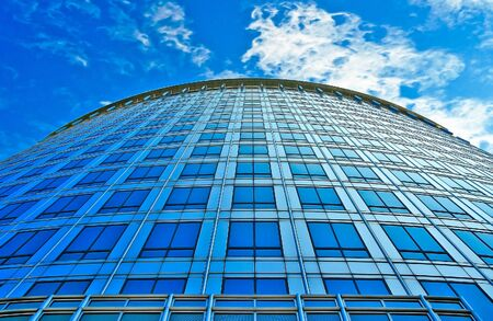 A view up the side of a building with a sky background. photo