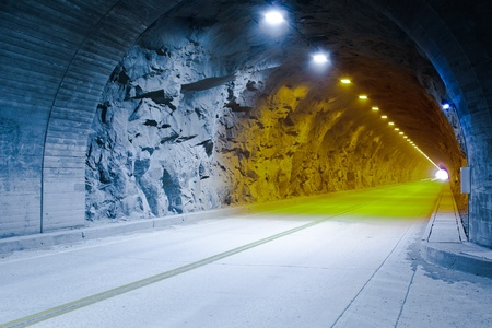 A roadway making a straight line through a granite tunnel with lights.