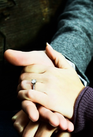 Newly engaged couple holding hands with the engagement ring showing. Stock Photo