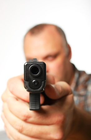 A man in a shirt pointing a handgun with a white background.