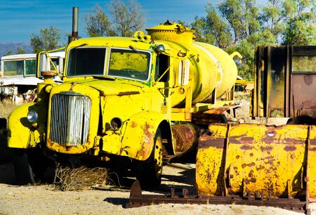 Yellow water truck rusting and becoming decrepit in a desert junk yard.