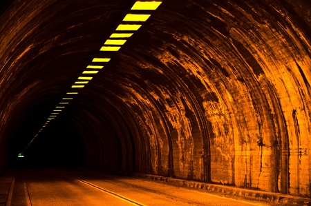 Tunnel, sidewalk, roadway and lights leading to a far away exit. Stock Photo - 11505925