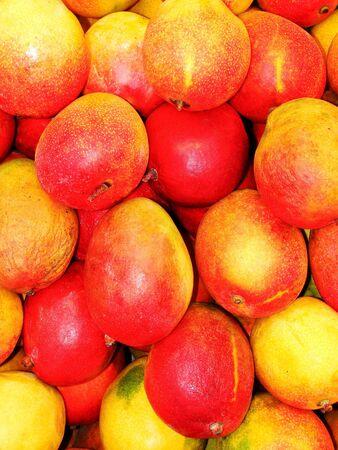 Basket mangos bunched together in a fruit market.