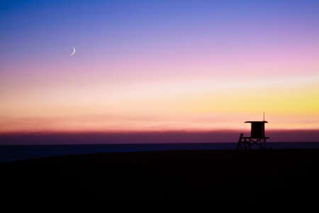 A lifeguard tower in Newport Beach, at sunset with the moon. photo