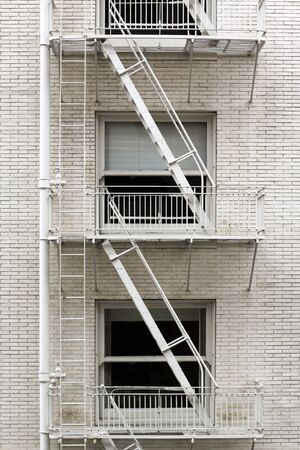 brownstone: Fire escape ladder zigzagging across the face and windows of a brownstone that