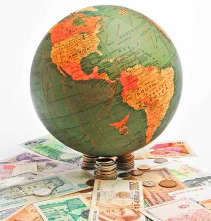 World globe showing the northern and southern hemispheres with world currency. Stock Photo