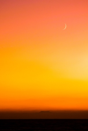 Sliver Moon appearing above a distant island at sunset.