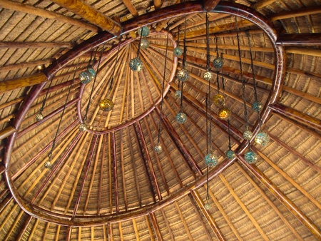 The indoor section of a palapa roof decorated with glass balls hanging on string. Stock Photo