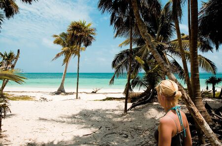 Woman discovering a secret white sand beach in the Riviera Maya area of the Yucatan Peninsula.