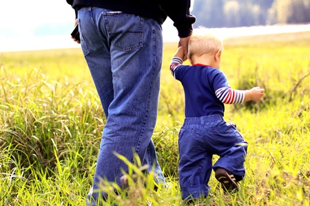 Young boy walking with his father in a grassy field. photo