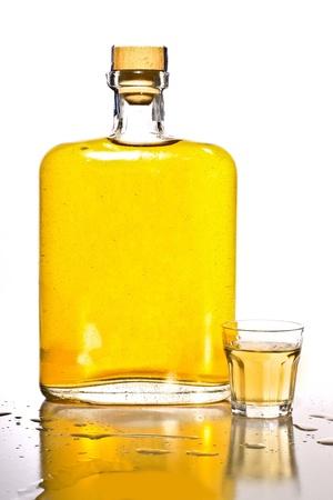 botella de whisky: Botella sin etiqueta de tequila con un vaso lleno.