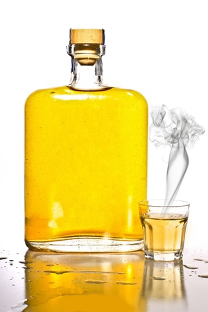 Unlabeled bottle of tequila with a filled shot glass with smoke. Stock Photo