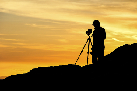 tripod mounted: Landscape photographer with a tripod mounted camera profiled against the sunset. Stock Photo