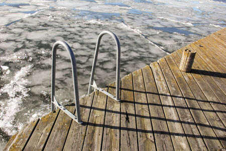 hand rails: Hand rails on a wodden deck in winter descend into a frozen lake.