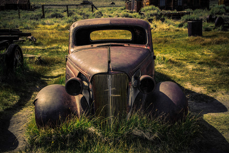 An abandoned car on the front lawn of a  prairie farm. photo