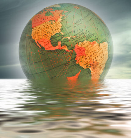 placid water: World globe showing the northern and southern hemispheres over placid water.