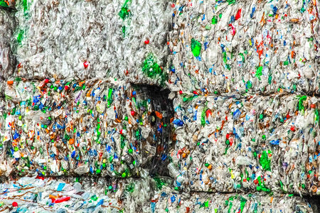 Square bales of wrapped plastic bottles ready for the melting process. Stock Photo