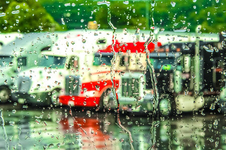 18 wheeler: Rain streaming down a window with 18 wheeler trucks in the background. Stock Photo