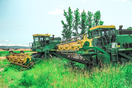 machinery: Wheat combines in a grass field during the off-season. Stock Photo
