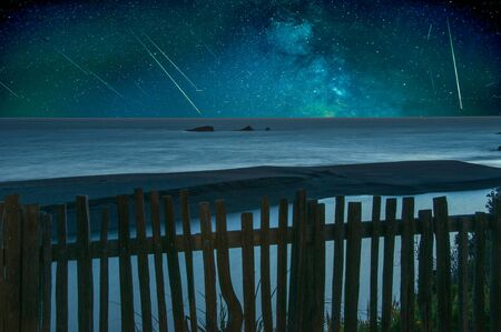 meteorites: Shooting stars falling over a tranquil ocean panorama.