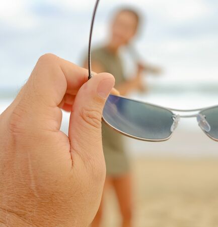 Mans hand holding a pair of glasses, with a woman in the background. Stock Photo