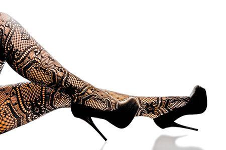 piernas de la mujer seductora con medias de diseñador y zapatos de tacón alto.