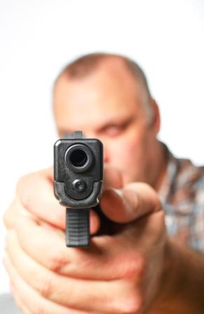 Photograph of a man pointing a handgun at the camera. Stock Photo