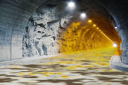 Una calzada acuosa haciendo una línea recta a través de un túnel de granito con luces.
