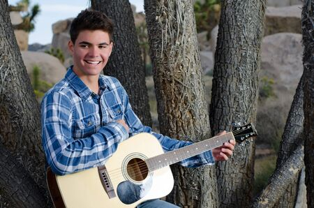 joshua: Young male model posing in front of a joshua tree in the desert with a guitar.