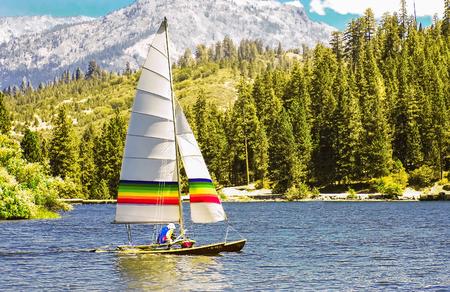 Catamaran sailing smoothly on the surface of a mountain lake. Stok Fotoğraf