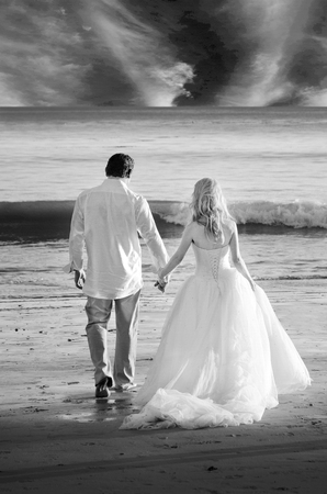 White dressed bride on a beach with a sailboat in the background.