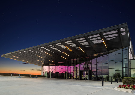 Modern glass building at twilight with stars and a clear blue sky. Imagens