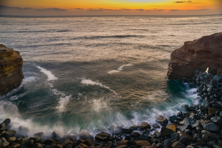 Long exposure image of Pacific Ocean surf pounding the rocks of a small cove in La Jolla, California.
