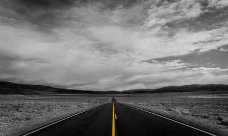 Yellow divider line on a monochrome image of a desert road going into the background.