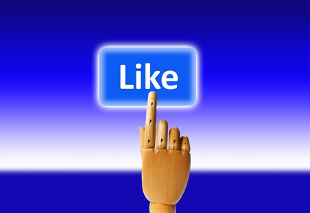 Wooden finger pressing a like button. Stock Photo - 9945171
