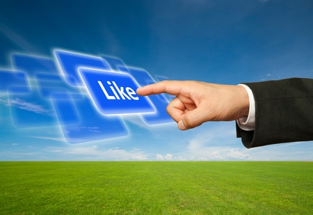 Ecological concept, finger of businessman pressing like blue button. Stock Photo - 9945245