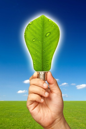 Ecological concept, leaf and lamp mixed together with hand  Stock Photo