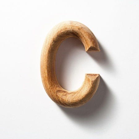Wooden alphabet letter with drop shadow on white background, C photo
