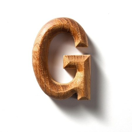 Wooden alphabet letter with drop shadow on white background, G photo