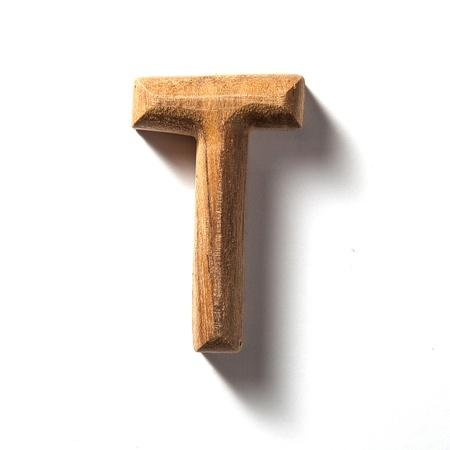 capitel: Letra del alfabeto de madera con sombra sobre fondo blanco, T