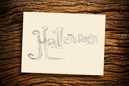 Hand writing Halloween on cream paper with ruin wood background photo