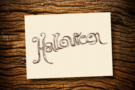 office party: Hand writing Halloween on cream paper with ruin wood background Stock Photo
