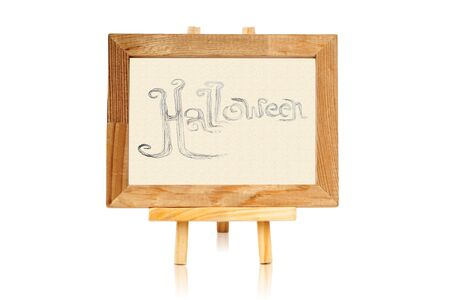 Hand writing Halloween on cream paper with wooden frame and stand photo
