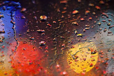Rain drops on windshield with colorful bokeh on background photo