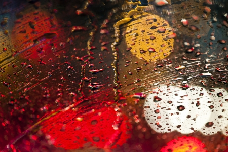 Rain drops on windshield with colorful bokeh on background
