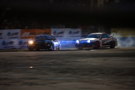 NONTHABURI THAILAND-JUNE 30 : Battle lap of two drift drivers at night time in D1 Grand Prix Series Thailand Professional Drift on June 30, 2013 in Nonthaburi, Thailand. Stock Photo - 24675386