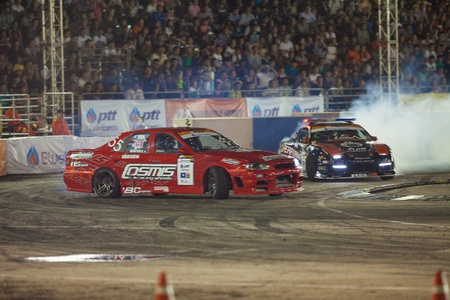 NONTHABURI THAILAND-JUNE 30 : Battle lap of two drift drivers at night time in D1 Grand Prix Series Thailand Professional Drift on June 30, 2013 in Nonthaburi, Thailand. Stock Photo - 21091504