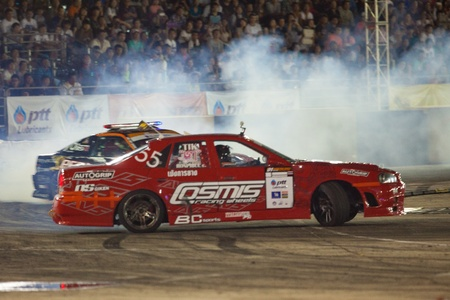 d1: NONTHABURI THAILAND-JUNE 30 : Battle lap of two drift drivers at night time in D1 Grand Prix Series Thailand Professional Drift on June 30, 2013 in Nonthaburi, Thailand.